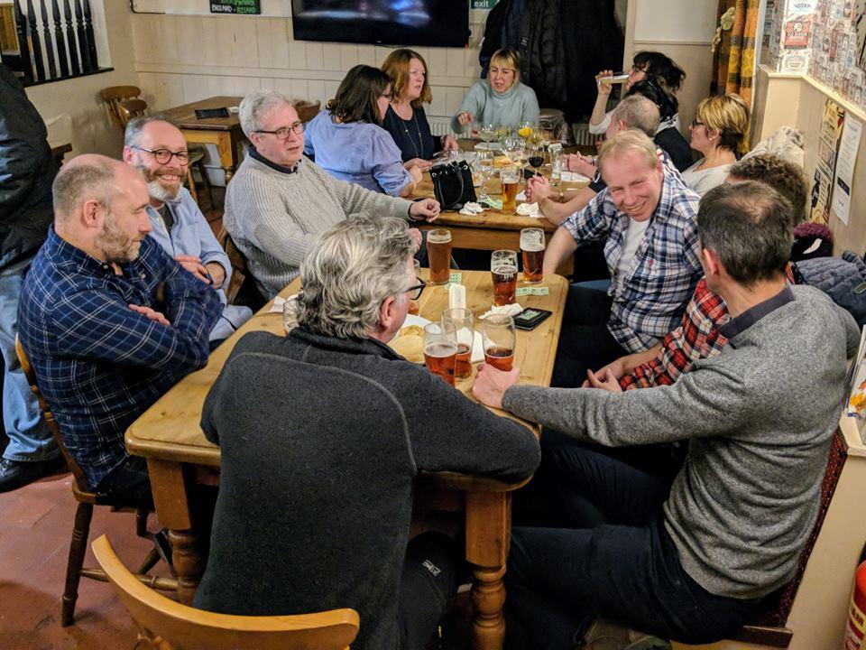 people at a pub drinking and smiling