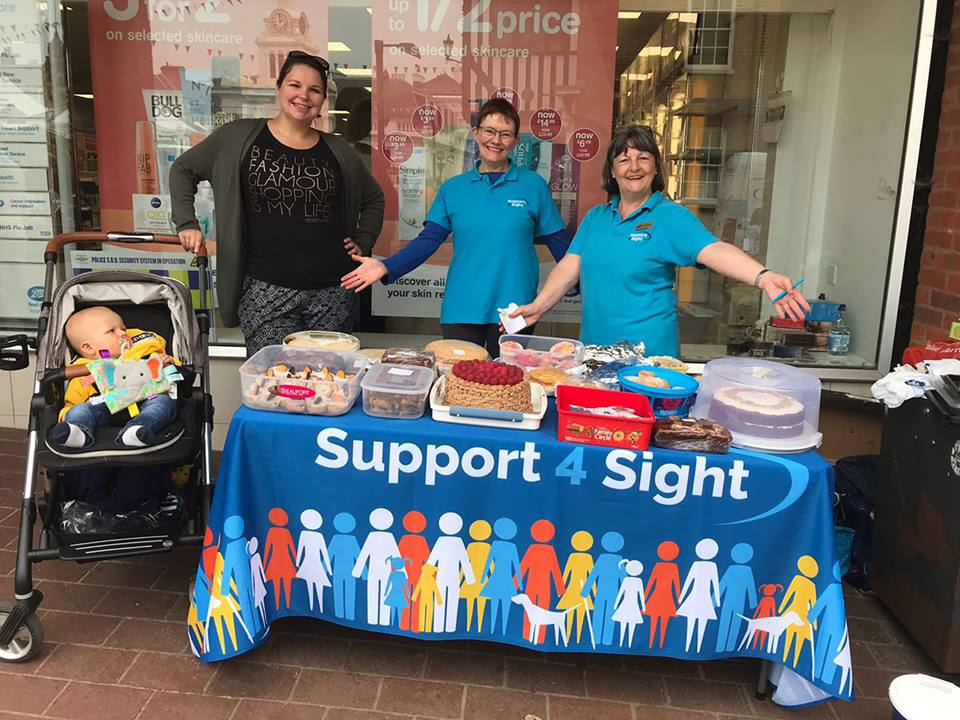 outside boots in saffron walden charity bake sale with a desk an lots of cakes to buy
