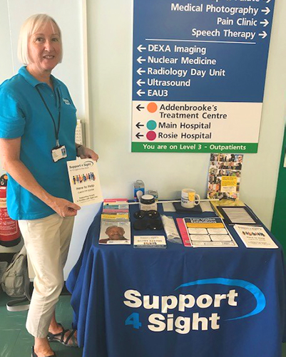Lady standing next to support for sights desk in addenbrooke's hospital