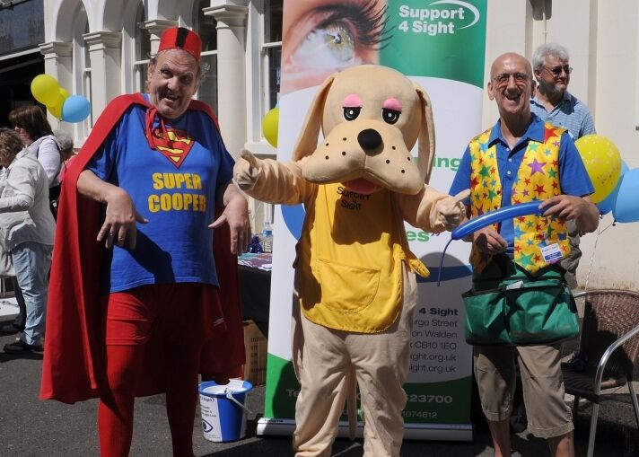 Semour and 2 men one dressed at super man and the other one a clown, at a fundraiser event on the market in saffron walden