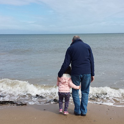 man and small child at beach