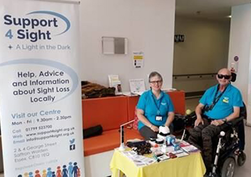 two people at the hospital desk with support for sight signs up